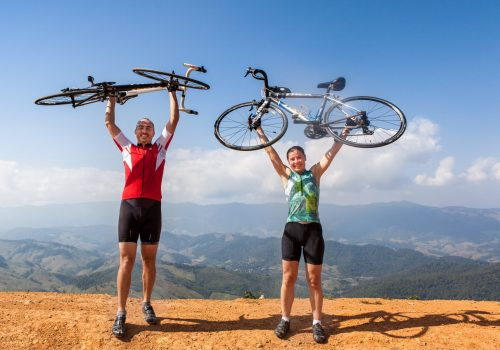 2 Cyclists holding their bike in the air