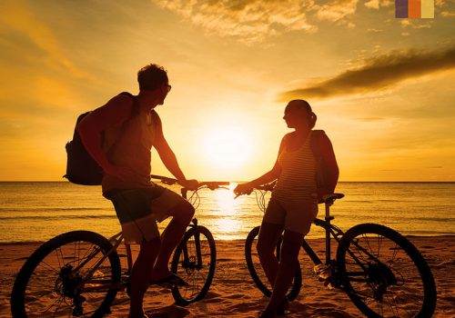 2 Cyclists enjoy the sunset at the beach