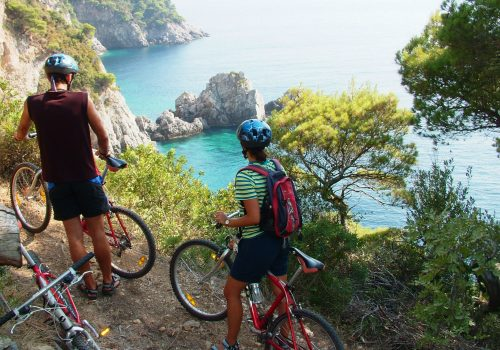 Two cyclists on a cliffside looking out over the sea in Croatia