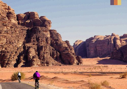 Cyclists ride in the red sand desert