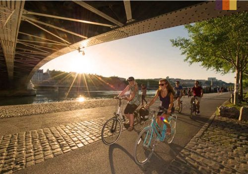 Cyclists ride along the Rhone River