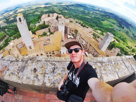 Man takes a selfie with the  town of San Gimignano