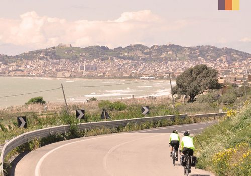 Cyclists ride next to the coast in Sicily