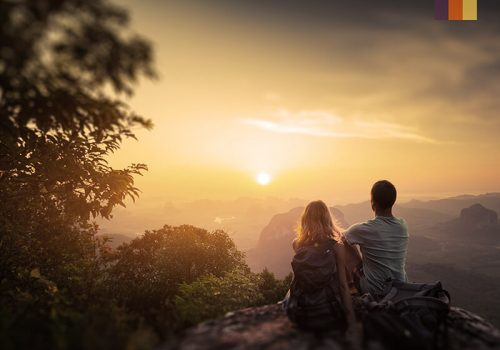 Couple looks to the sunset on a mountain