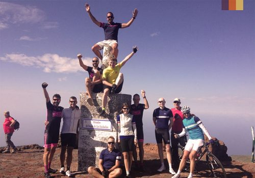 Cyclists take a group picture at a statue in Tenerife