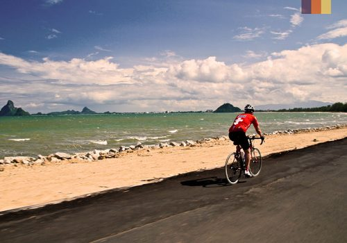 Cyclist rides along the coast of Thailand