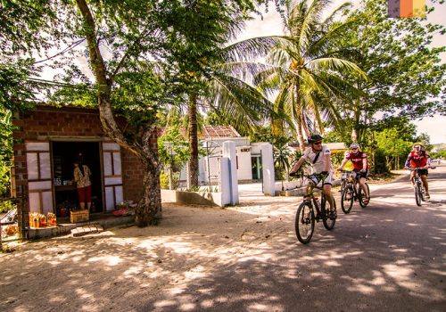 Cyclists riding through the Vietnamese villages