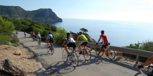 Group of cyclists ride along the coastline of Ibiza