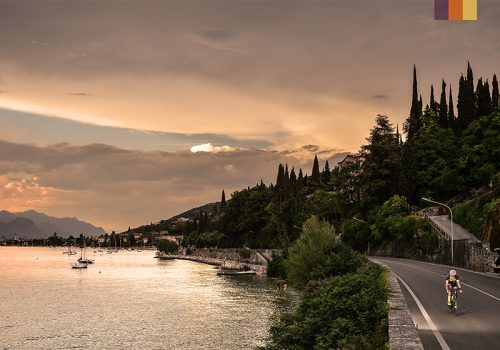 Cyclist rides alongside Lake Garda at sunset