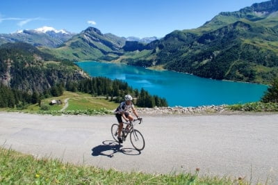 Cyclist rides alongside Lac de Roselend