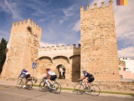 Cyclists ride along the medieval 14th-century walls in Alcudia