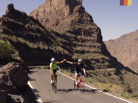 2 Cyclists holding hands to the top of the mountain