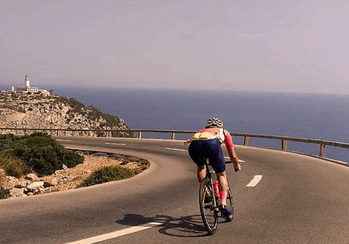 Cyclist rides in Mallorca with the view of a sea
