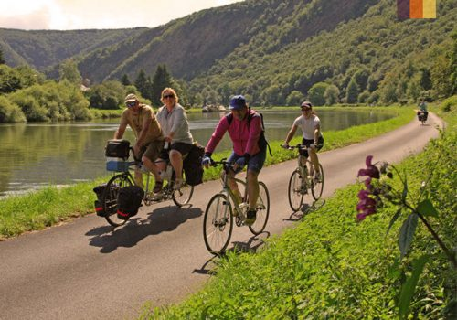 Cyclists ride along the riverside In Belgium
