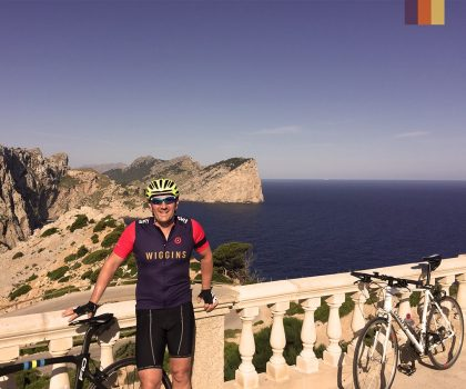 Man poses at the Cap Formentor Lighthouse in Mallorca with his bike