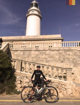 Woman poses with bike at the Cap Formentor Lighthouse