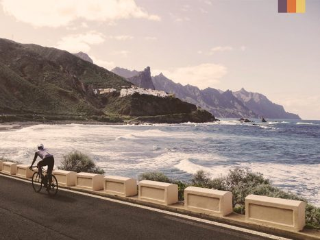 cyclist beside rugged tenerife Atlantic ocean coastline