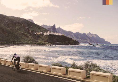 cyclist beside rugged tenerife Atlantic ocean coastline