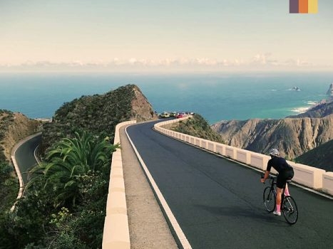 cyclist on a smooth tarmac road overlooking Tenerife's atlantic ocean coastline