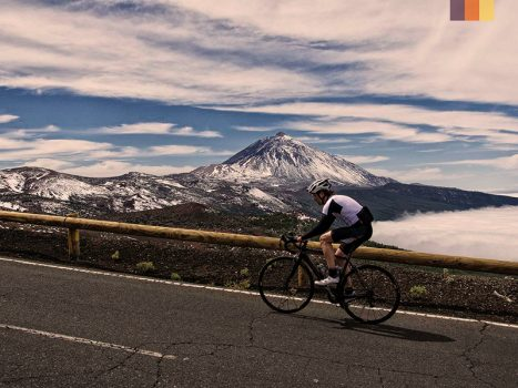 cyclist ascending a tarmac road with snow capped mount teide in the distance