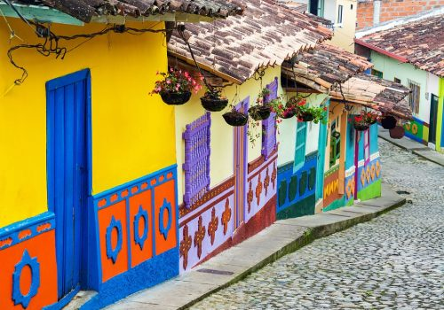 Buildings in Colombia, which are brightly coloured with patterns next to a cobbled street