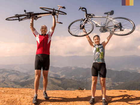 couple of cyclists holding up their bikes in front of vast landscape in thailand