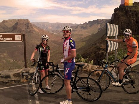 group of male and female road cyclists standing beside panoramic view of gran canaria mountains
