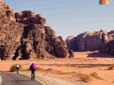 cyclists in the middle of a desert in jordan, with large sand mountains