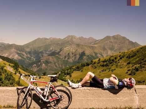 Cyclist lying on a wall at the top of the Col d'Aubisque