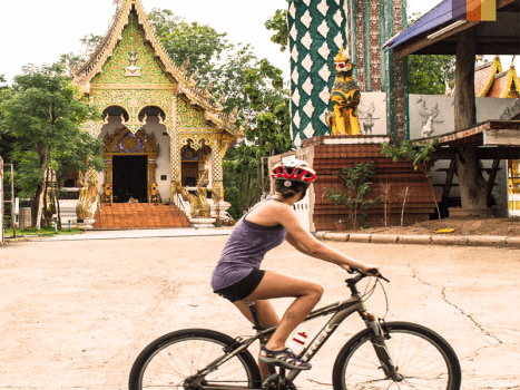 a female cyclist in front of a colourful temple in northern thailand