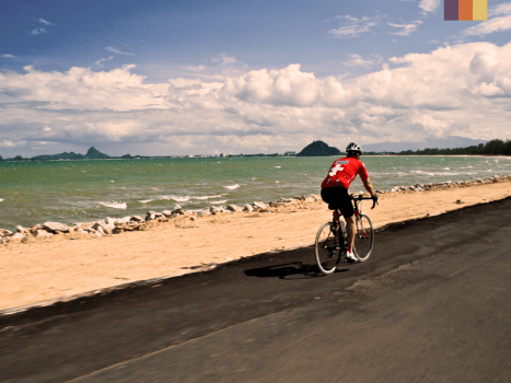 road cyclist cycling alongside a beach with clear blue sea and islands in the distance in south thailand