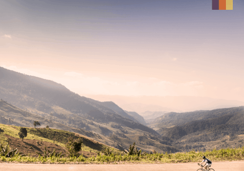 lone cyclist on smooth road with a backdrop of lush mountains and paddy fields in thailand
