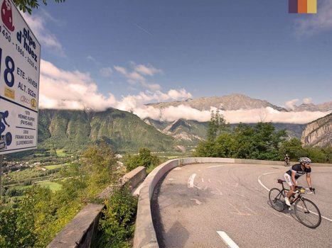 road cyclist pedalling up alpe d'huez, a famous climb from the tour de france overlooking the mountains