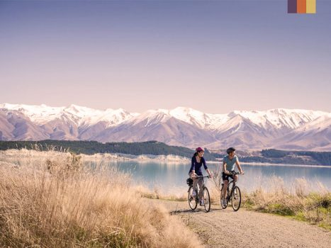 two cyclists on the otago rail trail in new zealand with snow capped mountains in the background