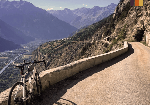 a road bike on a balcony road near alpe d'huez in france overlooking the alps mountains