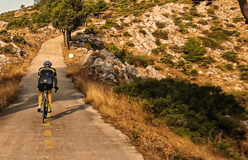 a road cyclist cycles up the hidden section of the coll de rates climb in costa blanca, spain