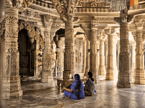 two indian women pray inside the ranakpur temple, which is an ancient jain temple in north india