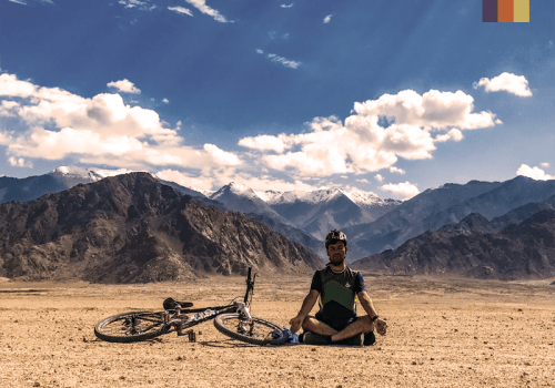 a cyclist meditates beside his mountain bike next to the himalays in northern india