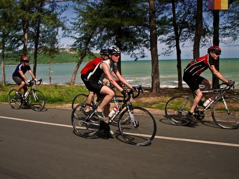 road cyclists cycling along the vietnamese coast clear blue sea