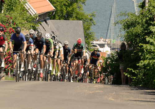 a group of cyclists cycle through a town near bastad in sweden