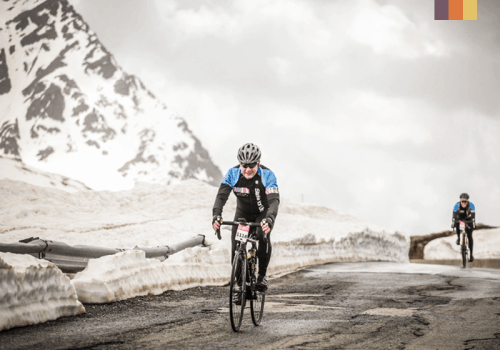 a road cyclist in cold weather on top of Passo Stelvio in Italy