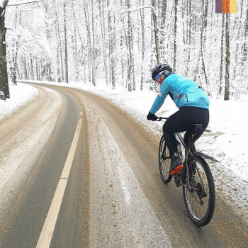 a cyclist on a snow road in lithuania