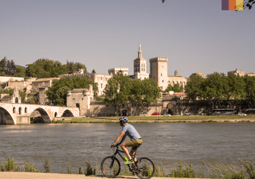 a cyclist travels along a traffic free path beside a river in a historic provence town, france