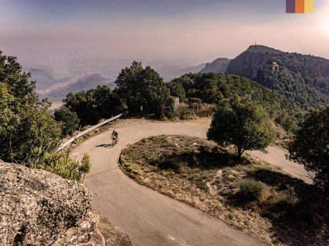 a road cyclist on a switchback bend on the rococorba climb in girona, spain