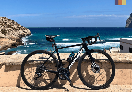 a road bike in front of the bright blue sea on one of the alternative cycling routes in mallorca
