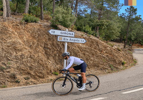 a road cyclist on the descent from els angels climb in girona, spain