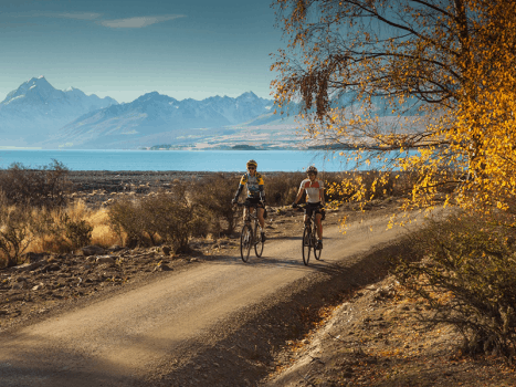 two cyclists on the alps to ocean cycle trail with mountains in the background