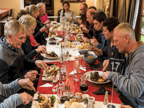 group of cyclists eating dinner at a restaurant in new zealand