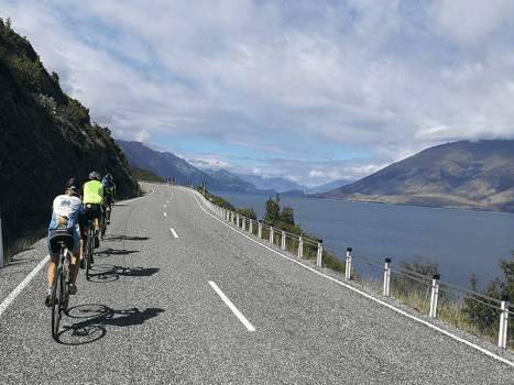 road cyclists on a tarmac road on the great west coast cycle ride in new zealand