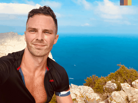 a cyclist takes a selfie high up a cliff in mallorca, with the blue sea in the background